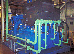This photo shows a large piece of equipment (an air compressor) connected to pipes that run vertically down from the ceiling. The pipe then run alongside the main body of the equipment and connect to the right side of the equipment. A large black box sits on top of the main body of equipment.
