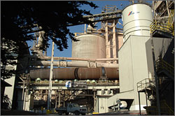 Photo of a cement manufacturing plant showing a large vertical kiln with horizontal pipes in front of the kiln. A truck on the ground shows the large scale of the plant.