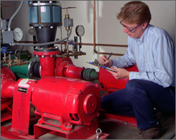 Photo of a man crouching next to a red electric motor and taking notes on a notepad.