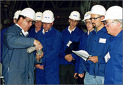 This is a photo of a group of men in hardhats centered around an instructor demonstrating a technique in an industrial plant environment.