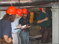 Photo of three students and a faculty member from the University of Dayton Industrial Assessment Center; all are standing under insulated metal piping and taking or recording efficiency and performance measurements of heating and cooling equipment at a heat-treating plant.
