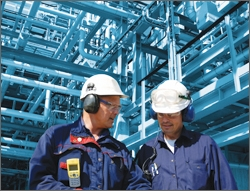 Photo of two men in hardhats conferring in front of an industrial plant background.