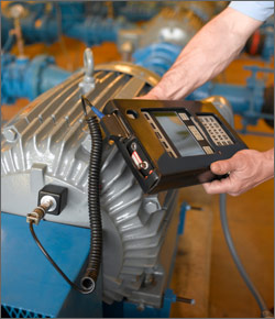 This photo shows a motor in an industrial plant environment which is being measured by a person holding a square testing device with a screen. The testing device is connected to the motor by a cable.