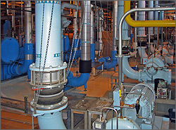 This photo shows an industrial chilled water system, which appears as several vertical pipes, motors, and valves.