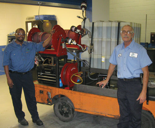 Stephen Leard (right) and Manvil Johnson (left) stand in front of their mobile lubrication cart at the Power Partners Inc. plant in Athens, Ga.