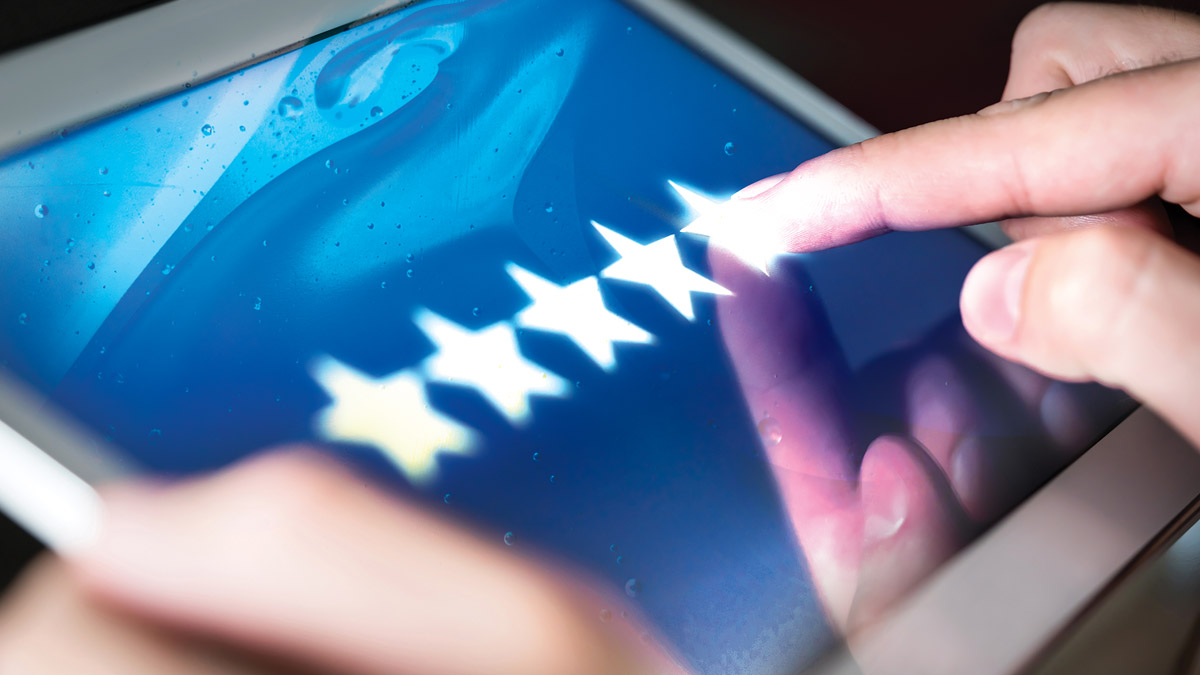 A close-up shot of hands holding a tablet. The tablet displays an image of five stars in a row. The tablet user is touching the furthest right star, implying the user is giving a perfect (or five-star) review